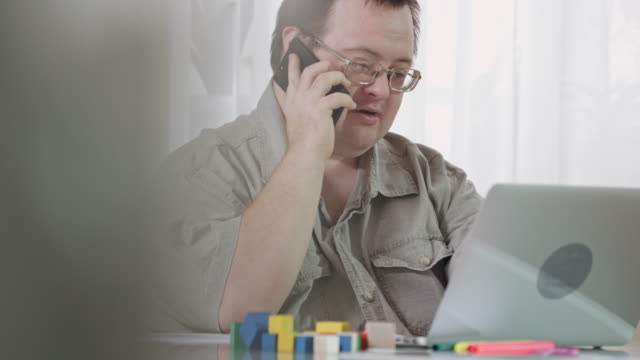 vídeos de stock e filmes b-roll de busy man with down syndrome working at home - acessibilidade