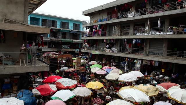 A busy market in Accra, Ghana where umbrellas protect vendors 3