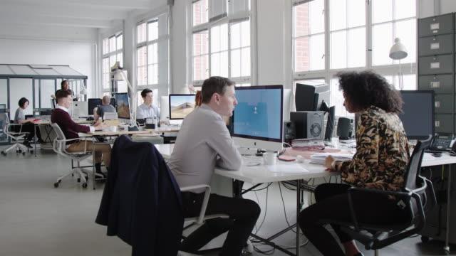 働く人々と忙しい現代のオープンプランオフィス - フリーアドレス点の映像素材/bロール