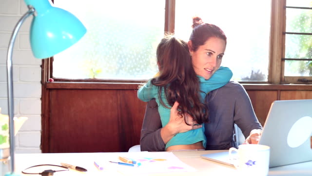 Busy mother at home office desk while daughter hugs her