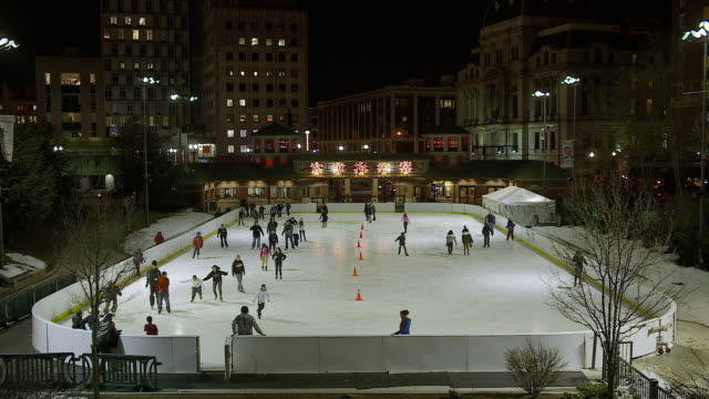 busy outdoor ice skating rink in city surrounded by tall buildings at night - ice rink stock videos and b-roll footage