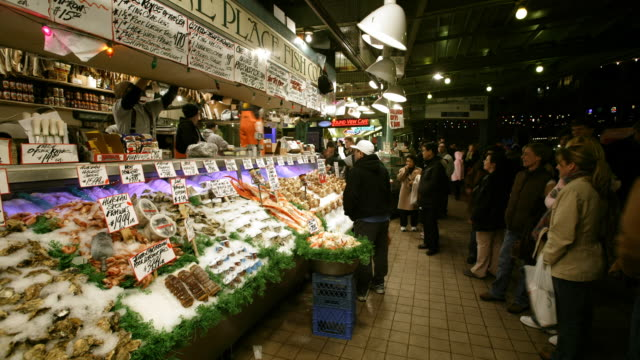 a busy outdoor market at night - pike place market stock videos and b-roll footage