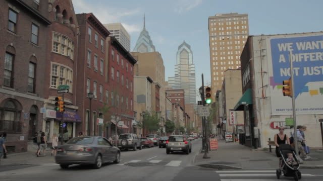 la busy pedestrian and vehicle street traffic with one and two liberty place skyscrapers towering over older section of the city / philadelphia, pennsylvania, united states - philadelphia pennsylvania video stock e b–roll