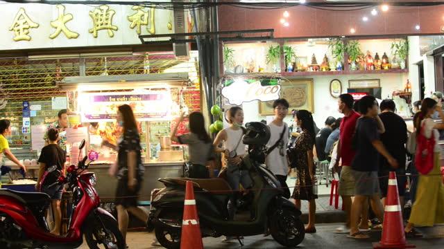 vídeos de stock e filmes b-roll de busy pedestrians and cars on bangkok chinatown yaowarat road at night - bangkok