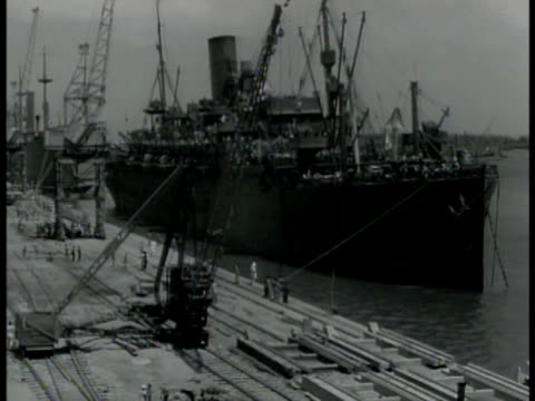 busy port w/ barrage balloons above harbor. us transport ship in dock. us allied soldiers standing on ship's deck. us soldiers walking down ship's... - kolkata stock videos & royalty-free footage
