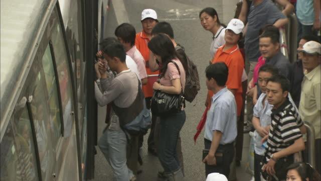 ws ha tu td busy road with passengers boarding bus at bus stop, beijing, china - バス停留所点の映像素材/bロール