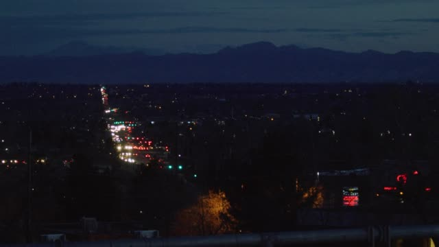 a busy road/highway in denver at night illuminated by headlights and tail lights with the rocky mountains in the background - televisione a ultra alta definizione video stock e b–roll