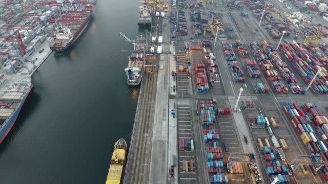 vídeos y material grabado en eventos de stock de a busy seaport with the berth and piles of containers - java
