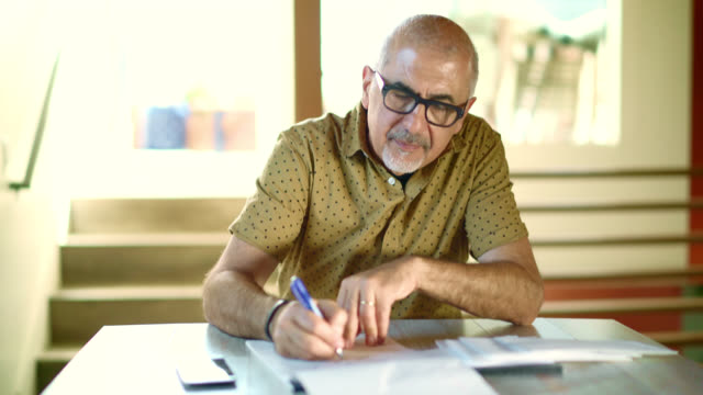 vídeos de stock e filmes b-roll de busy senior man working with mail correspondence: responding the phone call, writing, opening the envelop, reading the letter. - correspondência