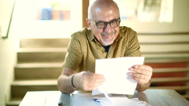busy senior man working with mail correspondence: responding the phone call, writing, opening the envelop, reading the letter. - post structure stock videos & royalty-free footage