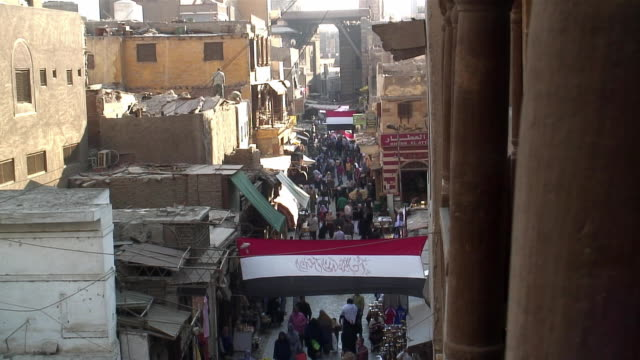 stockvideo's en b-roll-footage met ws ha busy shopping street in khanal khalili district, egyptian flag hanging over street / cairo, egypt - caïro