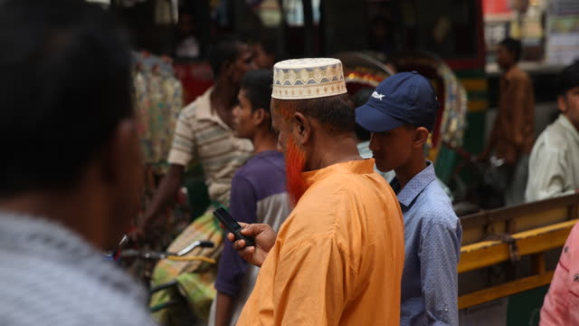 vidéos et rushes de busy situation in the streets of dhaka with many people moving through the crowds a muslim standing in a crowd of people with his mobile phone is... - pousse pousse