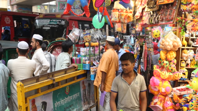 vídeos de stock e filmes b-roll de busy situation in the streets of dhaka with many people moving through the crowds a muslim standing in a crowd of people with his mobile phone is... - expansão urbana