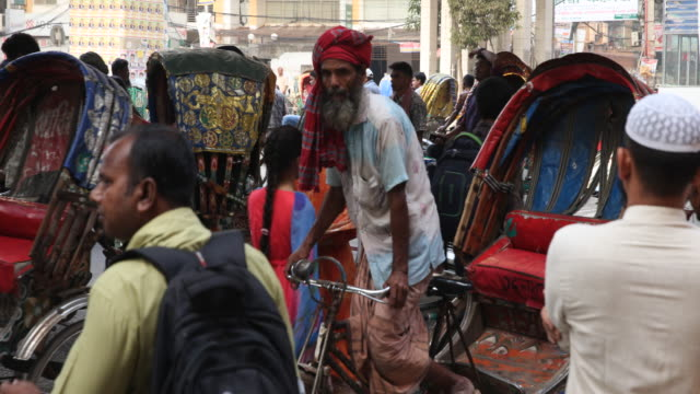 Busy situation in the streets of Dhaka with many people moving through the crowds the residents of Dhaka use colorful rickshaws to get themselves...