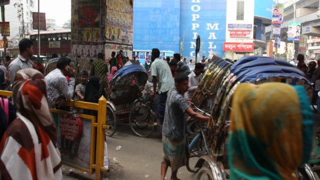 Busy situation in the streets of Dhaka with many people moving through the crowds