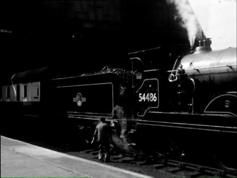 ms busy station and people buying tickets and some waiting for train / snow don, snowdonia, wales   - 1960年点の映像素材/bロール