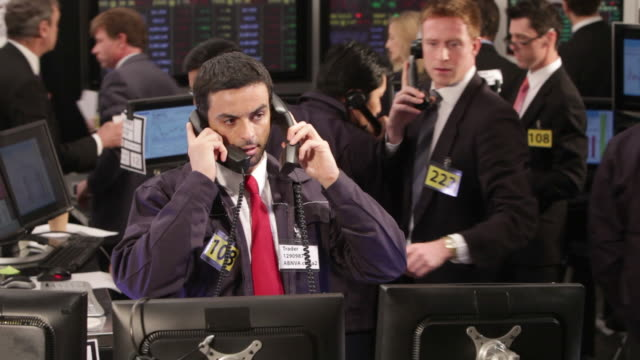 Busy stock brokers communicating over the phone in a Stock Exchange