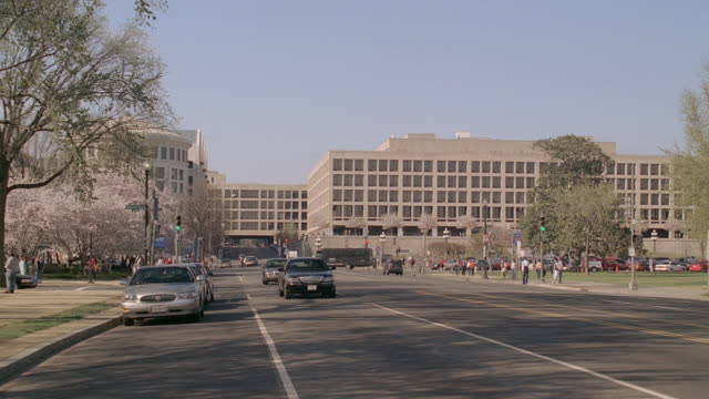 pan busy street in front of the capitol building with cars driving by and people walking in the park / washington, dc, united states - スウィッシュパン点の映像素材/bロール