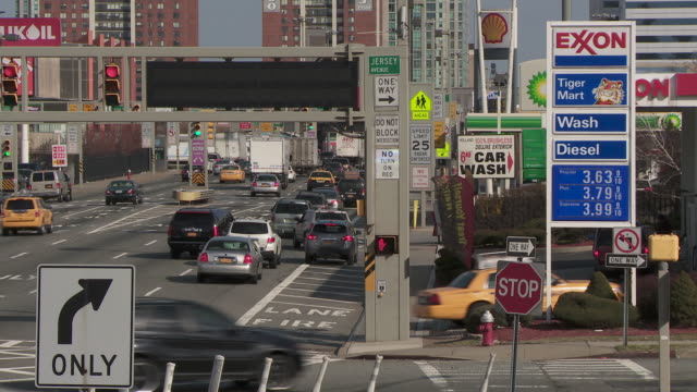 a busy street in jersey city with gas stations stacked up and crazy driving past to enter new york through the holland tunnel - ジャージーシティ点の映像素材/bロール