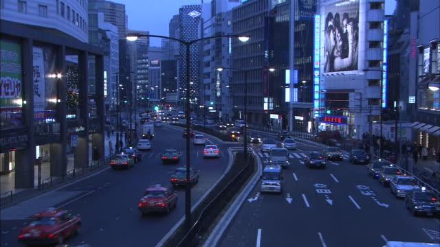 vídeos de stock e filmes b-roll de busy street in tokyo at dusk - figura feminina