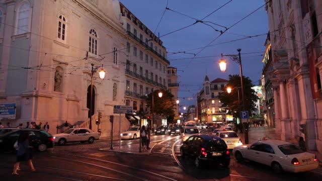 ws busy street intersection at dusk / lisbon, portugal - 路面軌道点の映像素材/bロール