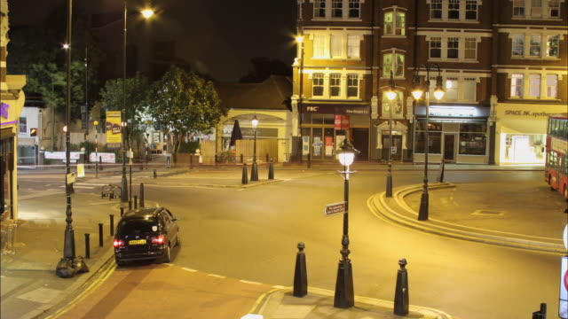 t/l ws ha busy street intersection at muswell hill at night / london, united kingdom - autobus a due piani video stock e b–roll