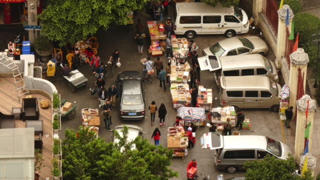 busy street market in guangzhou, china from above. loctated in front of sacred heart cathedral - spoonfilm stock-videos und b-roll-filmmaterial