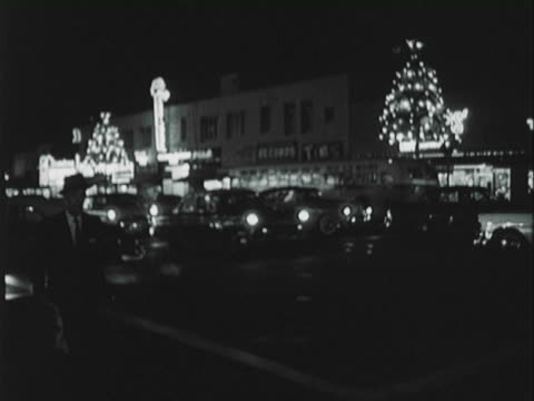 montage busy street traffic and shoppers walking along the sidewalks passing storefronts at christmas time / los angeles, california, united states - anno 1957 video stock e b–roll