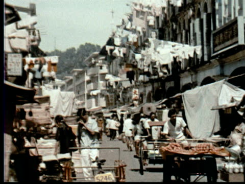 1957 MONTAGE Busy street w/ shops + hanging laundry. Hanging printed fabric. Man smoking cigarette / Singapore / AUDIO