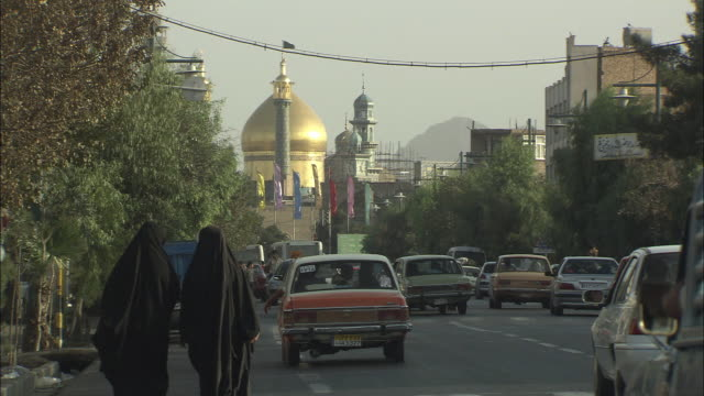 ws busy street with golden domed mosque in background / teheran, iran - hijab stock videos and b-roll footage
