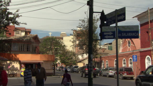 busy street with residential buildings, cristo de la concordia on san pedro hill in b/g, from av salamanca, cochabamba, bolivia - ボリビア点の映像素材/bロール