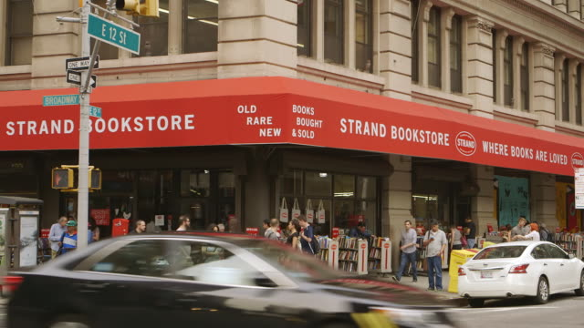vídeos de stock, filmes e b-roll de ws pan busy street with traffic in front strand bookstore / new york city, new york state, united states - livraria