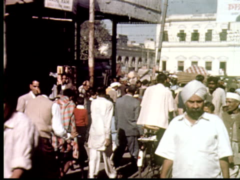 vidéos et rushes de 1960 montage busy streets in mumbai with pedestrians, trolleys, trucks, bicycles. outdoor market, street vendors, man tries on necklace / mumbai, india - 1960