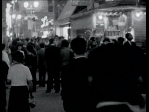 vídeos de stock e filmes b-roll de night busy streets pedestrians / neon signs sign for elia kazan's 'america america' buildings with flashing signs tokyo at night on october 16 1964... - 1964
