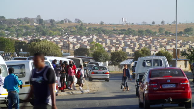 ws busy township street filled with cars, taxis and people, low cost housing in background / cosmo city, south africa - south africa stock videos & royalty-free footage