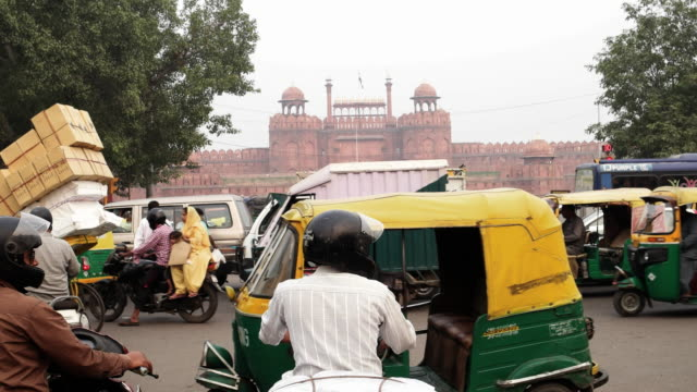 a busy traffic crossing in front of the red fort in the old delhi region of india - jinrikisha stock-videos und b-roll-filmmaterial
