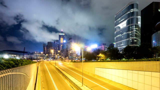 Busy traffic on multiple lane highway and buildings in hong kong at night,time lapse.