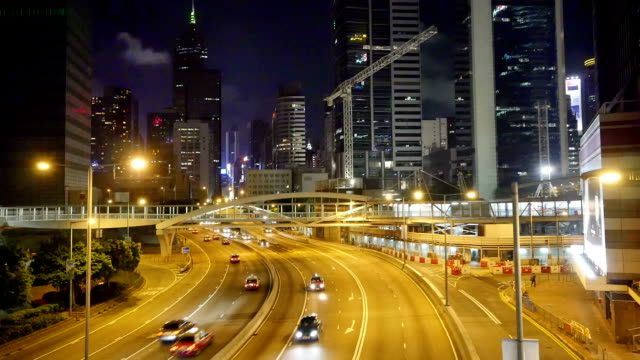 Busy traffic on multiple lane highway and buildings in hong kong at night,real time.