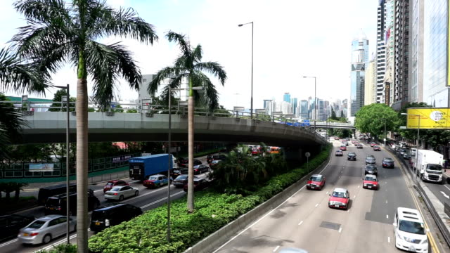 Busy traffic on multiple lane highway and buildings in hong kong,real time.