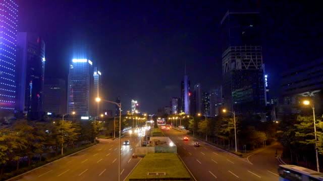 Busy traffic on multiple lane highway and buildings in shenzhen at night,real time.