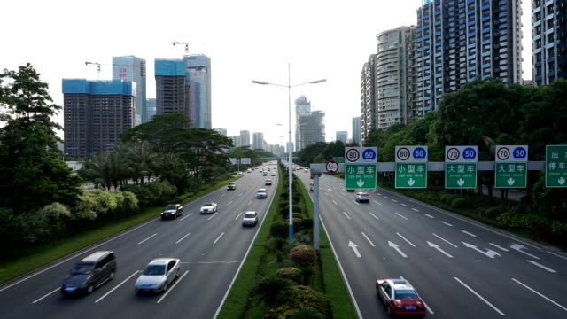 Busy traffic on multiple lane highway and buildings in shenzhen,real time.