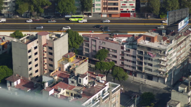 Busy traffic on roads and orange trains pass in Mexico City