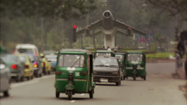 ms, selective focus, busy traffic on street, airplane monument in background , dhaka, bangladesh - dhaka stock videos and b-roll footage
