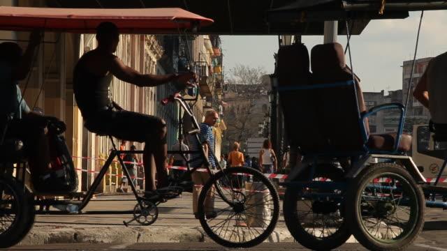 ms, busy traffic w/ pedicabs in havana, cuba w/ pedestrians and cars - fahrradtaxi stock-videos und b-roll-filmmaterial