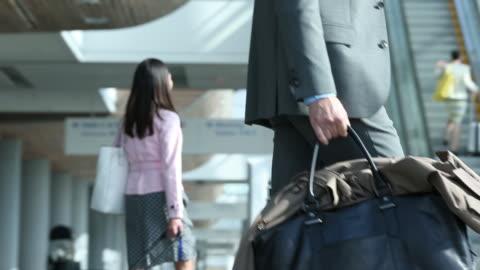 vídeos de stock, filmes e b-roll de busy travelers walking through airport - mala de rodinhas