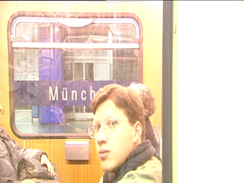 busy u-bahn underground train pulls in behind glass safety barrier passengers board and alight before train moves off munich - u bahnsteig stock-videos und b-roll-filmmaterial