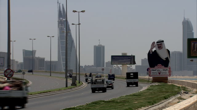 WS Busy vehicle traffic moving along highway with large roadside billboard of iconic figure saluting greetings, and skyline of Bahrain World Trade Center twin towers beyond / Manama, Bahrain