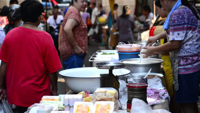 a busy vendor selling thai sweets on the street market in bangkok old town - thailand stock videos & royalty-free footage