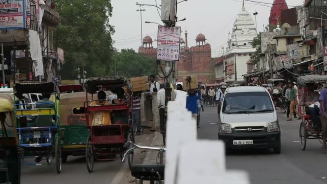 a busy view of a street in chandni chowk area of old delhi with the red fort in the background - new delhi stock videos & royalty-free footage