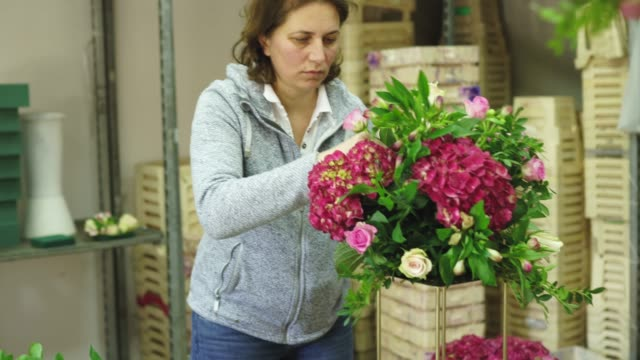 Busy woman florist working in flower workshop alone